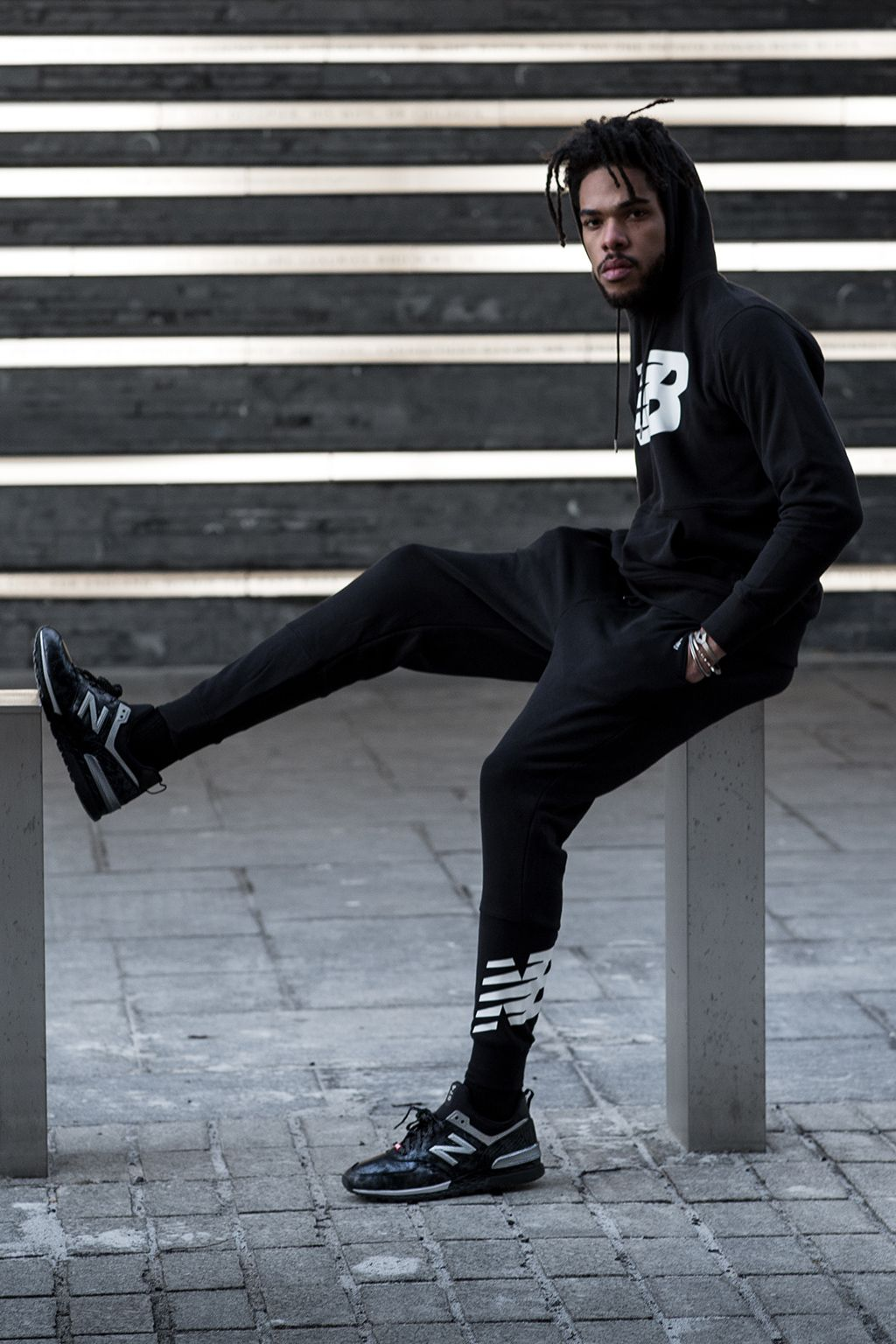 Evening photograph of male model posing with Black Panther New Balance shoes
